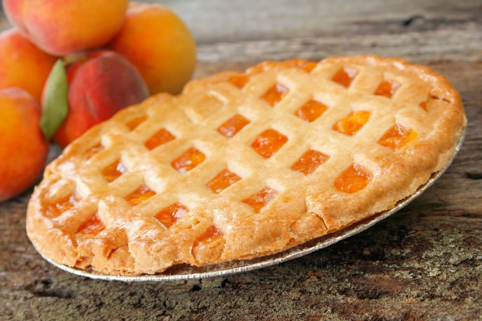Fresh baked peach pie with fresh peaches in the background.  Used a shallow depth of field with selective focus on the front edge of pie and crust.