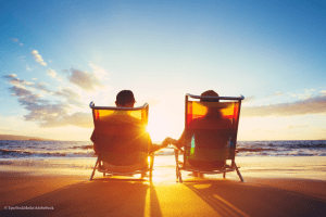 couple sitting on beach watching sunset during retirement after selling their business