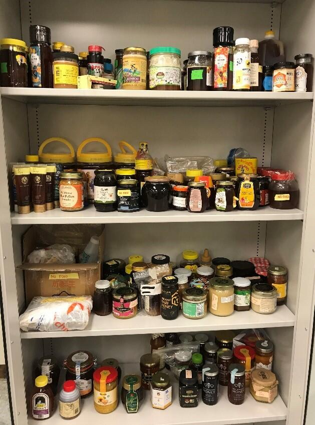 Variety of honey jars arranged in cabinet with four shelves.