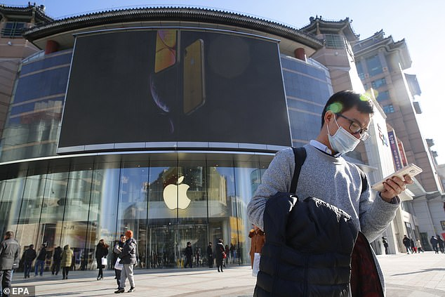 Apple products were once the most desirable electronic gadgets in China, but were priced beyond the reach of many.  Pictured, a man uses his phone outside an Apple store in Beijing