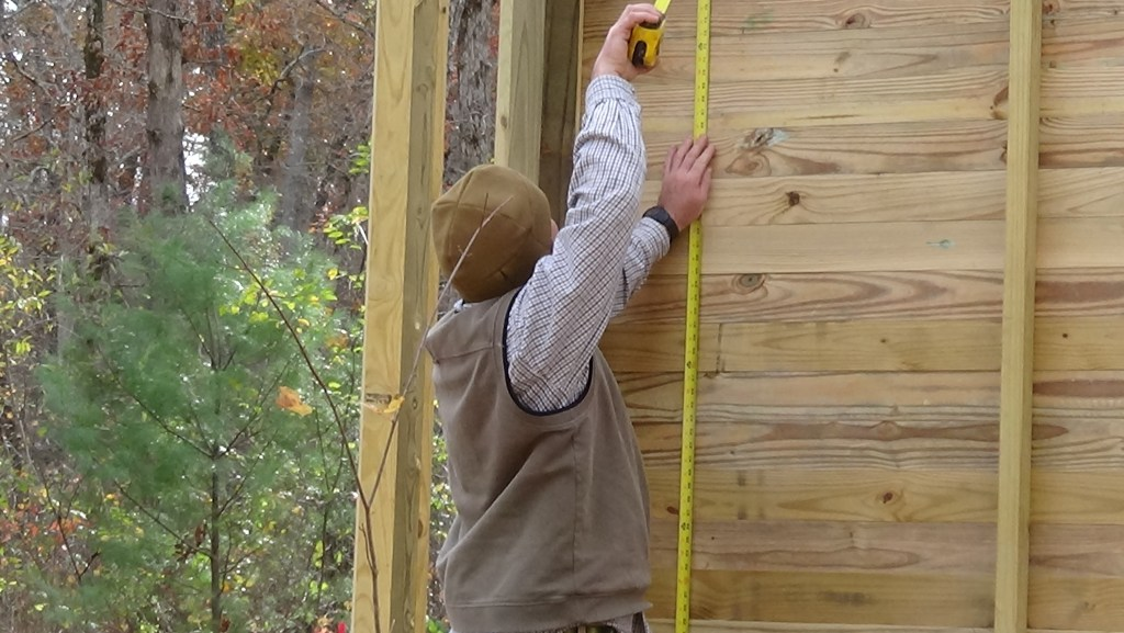 Boy Scout troop leader Chris Garner measures for doors to the aviary enclosures on Nov. 8, at Cumberland Mountain State Park.