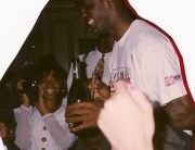 Diane, holding video camera, with Michael Jordan, holding a champagne bottle