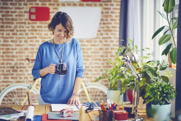 Portrait Of Female Designer Standing In Modern Office