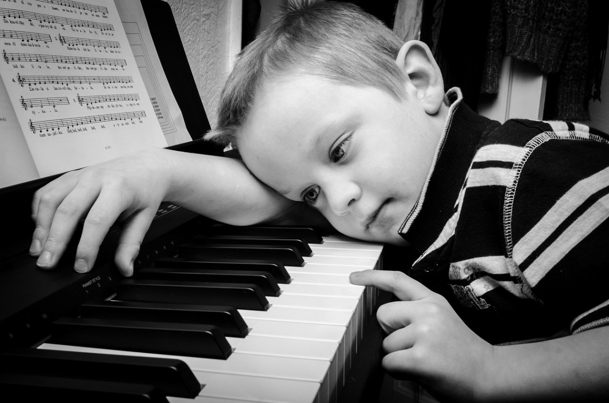 Sad kid at piano