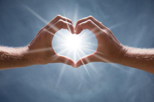 hands-heart-shape-rays-of-light