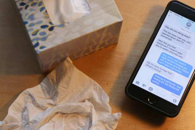 tissue box with crumpled tissue and cellphone