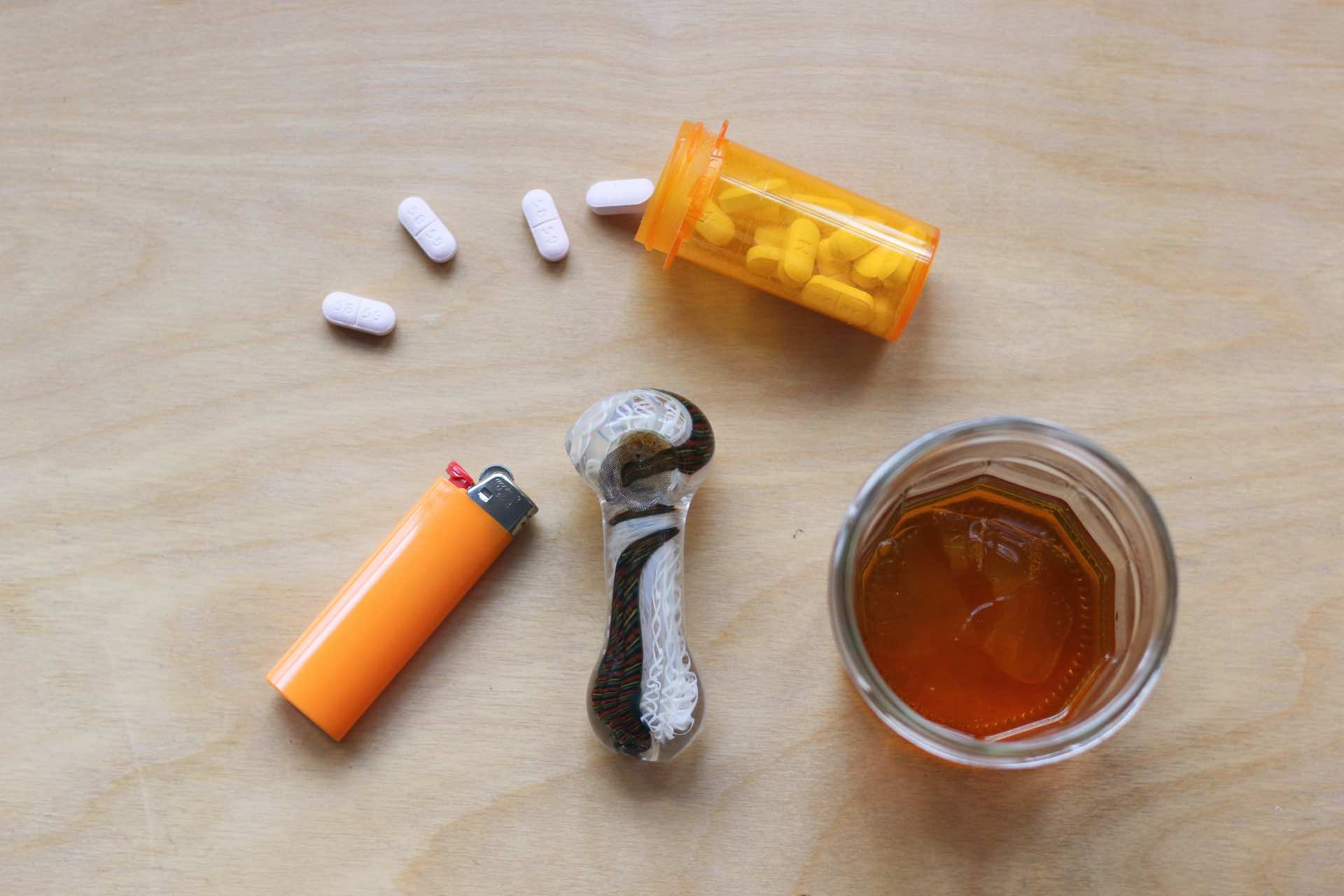spilled pills with lighter and pipe and whiskey glass