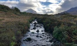 An image in Scotland with a rocky stream, pasture, and gorgeous sky.