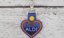 The 26 Best Things at Aldi post: image of Aldi heartshaped keychain with pouch for a cart quarter.