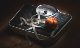 How I Finally Lost 25 Pounds (with Intermittent Fasting) Image of a scale with an apple and measuring tape