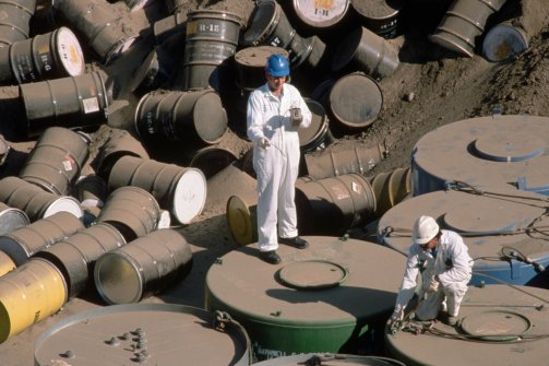 Barrels of low-level Class A commercial nuclear waste are checked with a Geiger counter in a trench at the Hanford Nuclear Reservation in Washington state on October 18, 1988. (Roger Ressmeyer/Corbis)