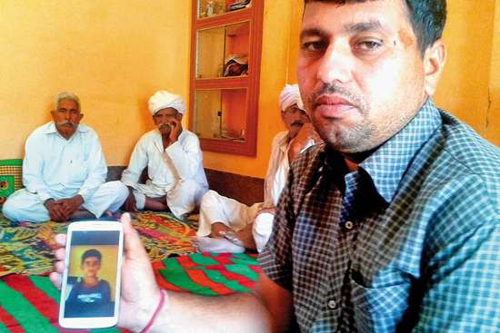 A relative holds up a picture of Neeraj