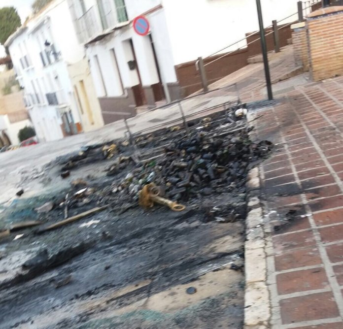 Un coche calcinado tras arder varios contenedores en la plaza La Constitución de Vélez