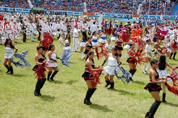 Las cachiporras y las bandas de paz mostraron sus habilidades artísticas y acrobáticas en el estadio Mágico González, donde al fondo, en los graderíos se observa el mosaico con la bandera de El Salvador. Foto Diario  Co Latino / Josué Parada