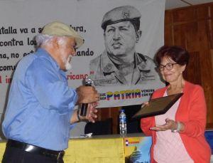 Carlos Brizuela, participante de la Cátedra Bolivariana, entrega un reconocimiento a la embajadora de Venezuela, Nora Uribe.  foto Diario Co Latino