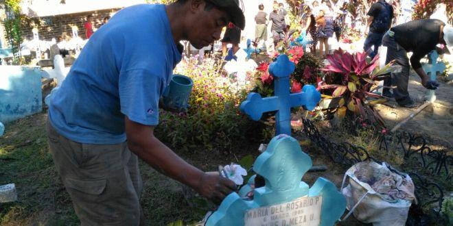 Entre azadones, oraciones y flores, salvadoreños recuerdan a sus difuntos