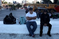Dos hombres esperan el llamado de los líderes de la caravana migrante que partió desde El Salvador del Mundo hacia la frontera de La Hachadura y luego hacia los Estados Unidos. Foto Diario Co Latino/ Davd Martínez.