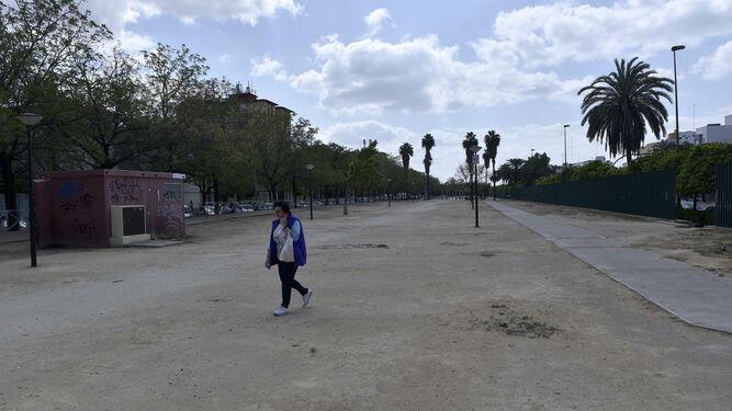 Una mujer cruza hablando por el móvil un tramo del bulevar de la Ronda del Tamarguillo que carece de sombra y mantenimiento.