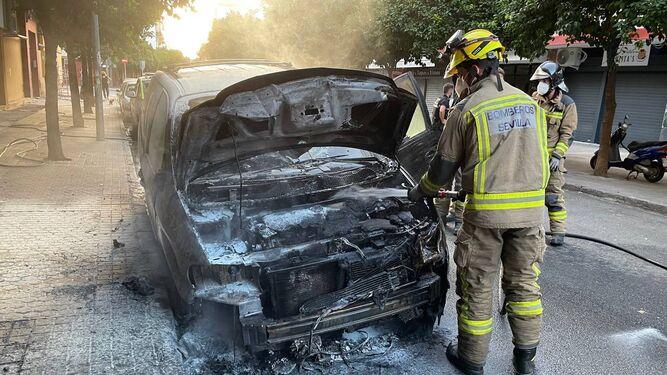 Los Bomberos apagan el incendio de uno de los coches quemados en la calle Venecia.