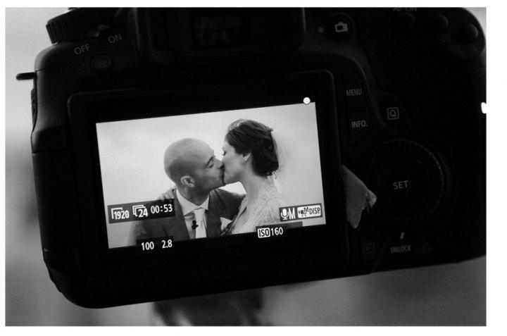 Camara con una pareja de novios besando en boda