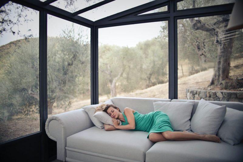 De Qué Lado es Mejor Dormir - mujer tumbada en el sofa