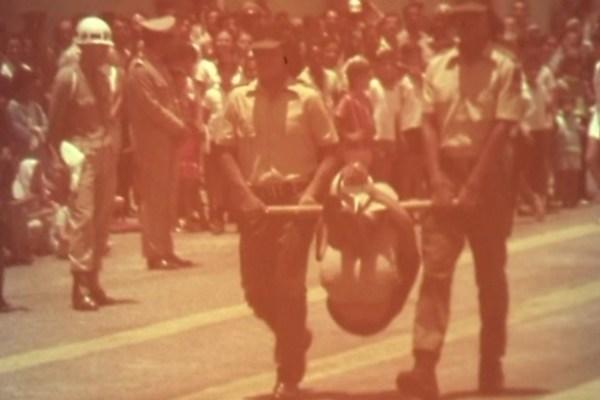 No desfile dos índios para as autoridades, um homem é carregado no pau de arara em público