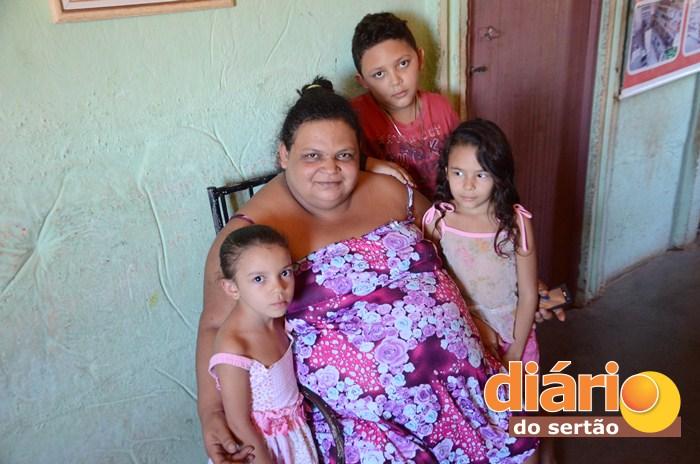 Mulher ao lado dos três filhos pequenos (foto Charley Garrido)