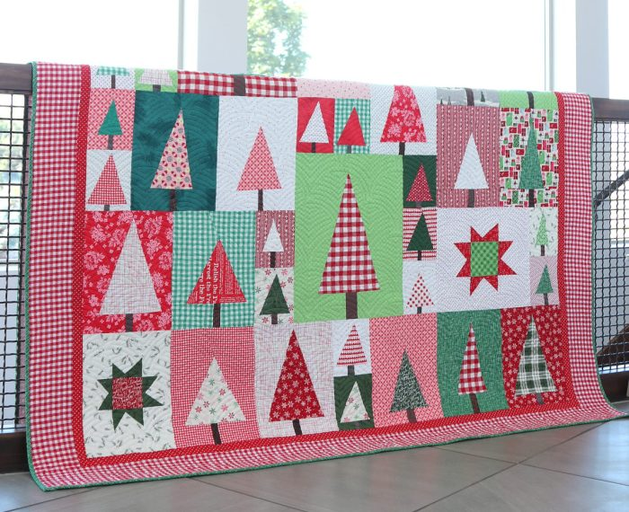 New Patchwork Forest Quilt Pattern: Pine Hollow Version by popular quilting blog, Diary of a Quilter: image of a red, white, and green patchwork forest tree quilt draped over a stair banister.