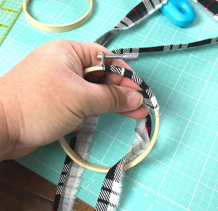 """Christmas in July - Hand Stitched Christmas Ornament Tutorial by popular sewing blog, Diary of a Quilter: image of a hand wrapping a 3/4"""" strip of black, white, and red fabric around a 3"""" embroidery hoop."""