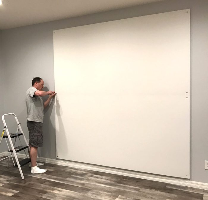 How to Build a Quilt Design Wall by Christa Watson by popular quilting blog, Diary of a Quilter: image of a man securing their quilt design board to a wall with a screw driver, screws, and washers.