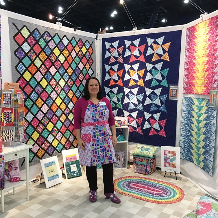 How to Build a Quilt Design Wall by Christa Watson by popular quilting blog, Diary of a Quilter: image of a woman standing in front of her quilt design walls with various quilts hanging on them.