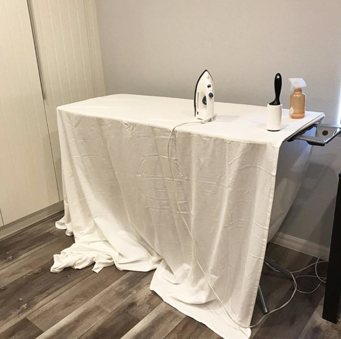 How to Build a Quilt Design Wall by Christa Watson by popular quilting blog, Diary of a Quilter: image of a king size white flannel sheet on an ironing board with an iron, lint roller, and spray bottle.
