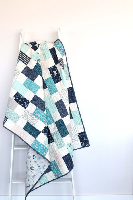 Bricks Baby Quilt Tutorial by popular quilting blog Diary of a Quilter: image of a various shades of blue bricks baby quilt hanging on a white ladder.