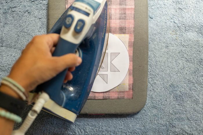 DIY Heirloom Christmas Ornament guest post by Coral + Co by popular Utah quilting blog, Diary of a Quilter: image of a woman ironing an Ohio star template to a square piece of Steam a Seam 2 that is on the backside of a piece of black and red plaid fabric.