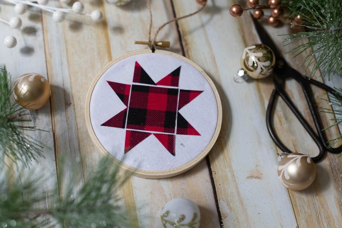 DIY Heirloom Christmas Ornament guest post by Coral + Co by popular Utah quilting blog, Diary of a Quilter: image of a finished embroidery hoop heirloom christmas ornament with a red and black plaid Ohio star, sewing scissors, white and gold ornaments, and pine tree branches.