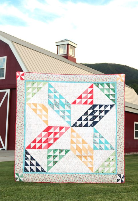 Sugarhouse Park Fabric Collection by Amy Smart by popular Utah quilting blog, Diary of a Quilter: image of a quilt made out of Sugarhouse Park fabric displayed outside in front of a red barn.