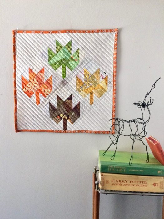 Scrappy Maple Leaf Quilt Pattern Tutorial by guest writer Leila Gardunia by popular quilting blog, Diary of a Quilter: image of a maple leaf quilt hanging on a wall.