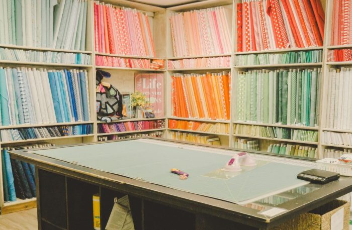 Shop Local - My Girlfriend's Quilt Shoppe + Giveaway by popular Utah quilting blog, Diary of a Quilter: image of of fabric bolts and a cutting table inside My Girlfriend's Quilt Shoppe.