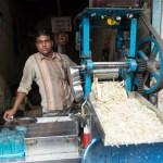 Juice vendor crushes sugar cane to serve fresh, sweet drinks.
