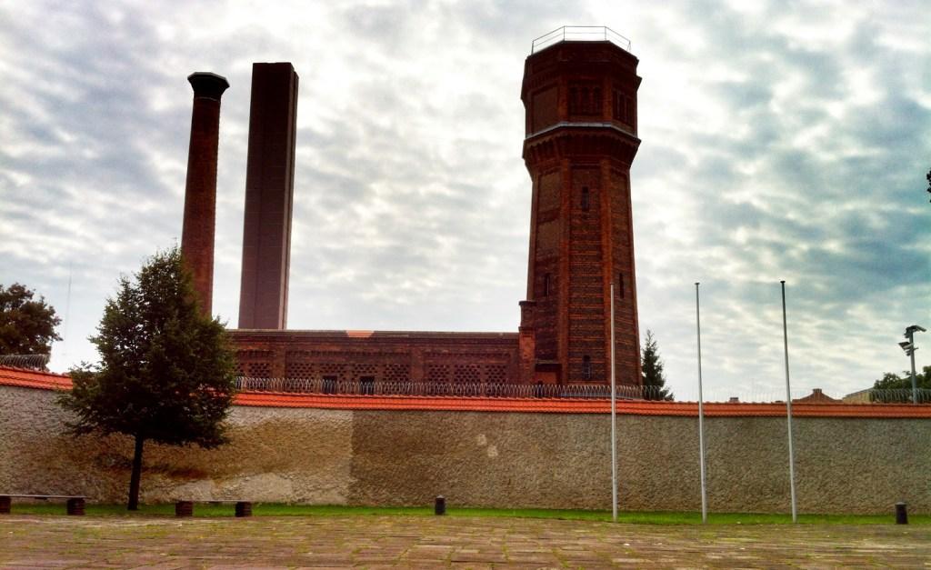 Sicht vom Innenhof der Gedenkstätte Plötzensee über eine Mauer mit Stacheldraht. Dahinter ragen große rote Türme aus Backsteinziegeln empor.