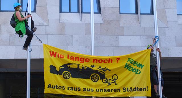 Robin Wood Aktivisten erklimmen die Fahnenstangen vor dem Verkehrsministerium und hängen ein Transparent auf.