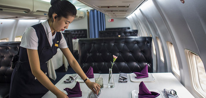 """A waitress finalizing the details of """"set up"""" tables before starting a shift meals."""