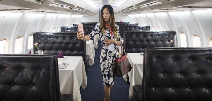 """Una mujer posa para un """"selfi"""" en el interior del Lily Airways, el primer avión-restaurante de China."""