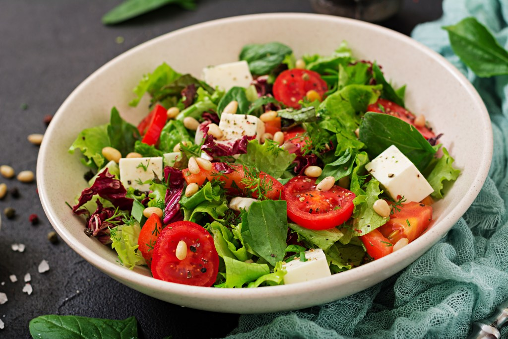 Dietary salad with tomatoes, feta, lettuce, spinach and pine nuts.