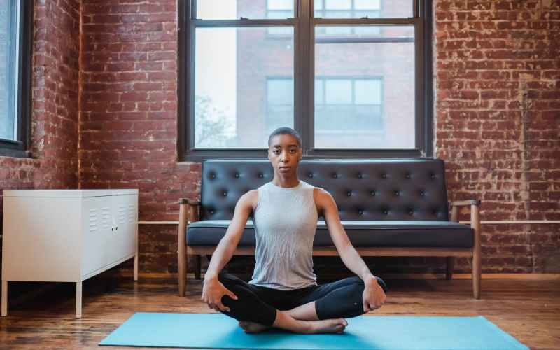 african american female meditating on yoga mat at home