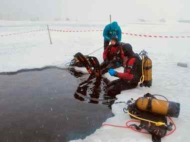 Deux plongeurs sous glace à Tignes se préparent à se mettre à l'eau