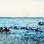 Trois plongeurs s'apprêtent à se mettre à l'eau
