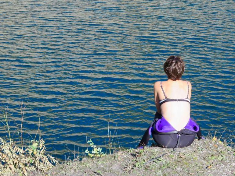 Une femme de dos regarde un plan d'eau