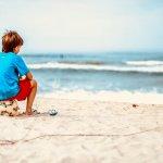 Un enfant assis sur sa balle de football regarde l'océan