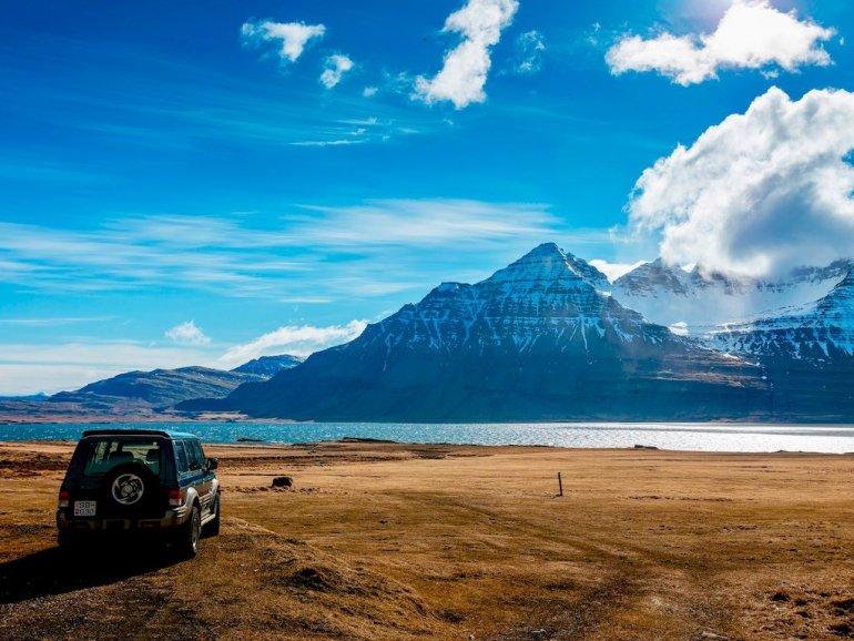 Un paysage d'Islande avec une voiture devant une montagne
